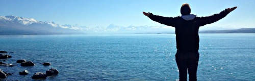 Student looking out at ocean with outstretched arms
